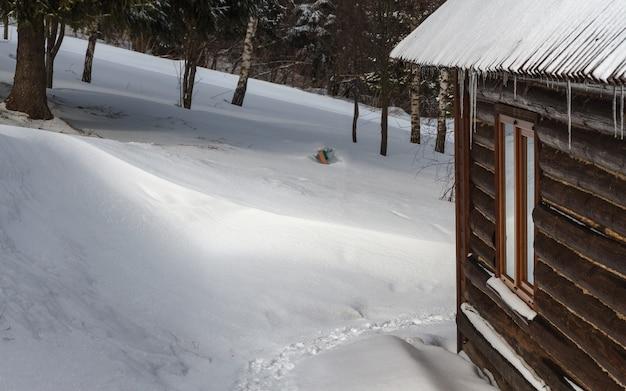 Casa de madera en la montaña en tiempo nevoso