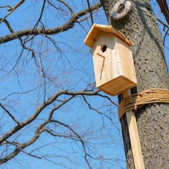 Casa de madera para pájaros en el árbol.