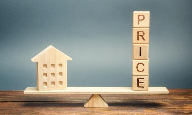 Casa de madera y la palabra precio en la balanza. concepto de propiedad de valoración justa. valoración de viviendas.