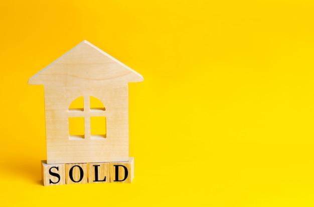 Casa de madera sobre fondo amarillo con la inscripción vendida.