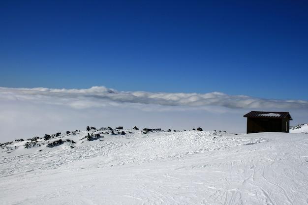 Casa de madera en el volcán etna cubierto por la nieve.
