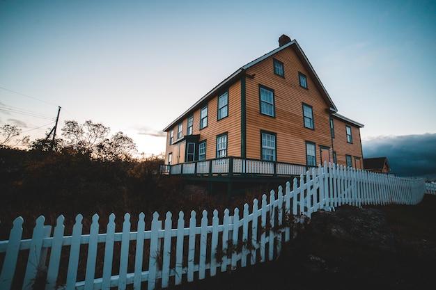 Casa marrón y blanca bajo un cielo blanco durante el día