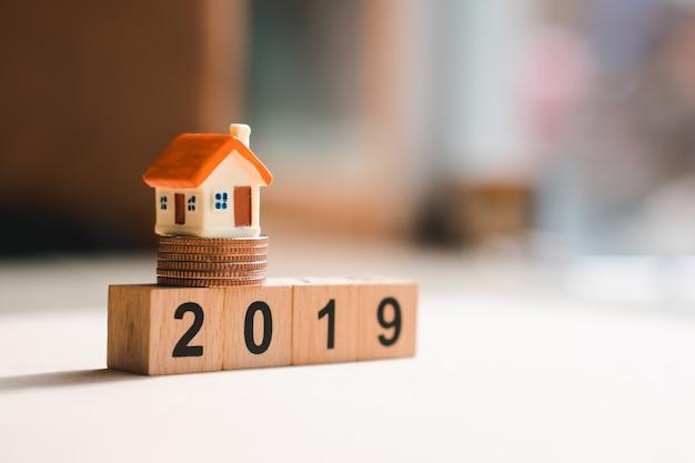Casa en miniatura en el bloque de madera 2019 con monedas de la pila
