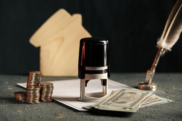 Casa en miniatura con dinero y papeles fiscales.