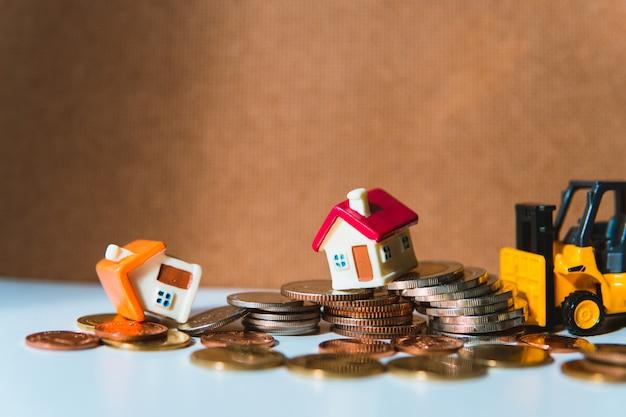 Casa en miniatura en pila de monedas con carretilla elevadora