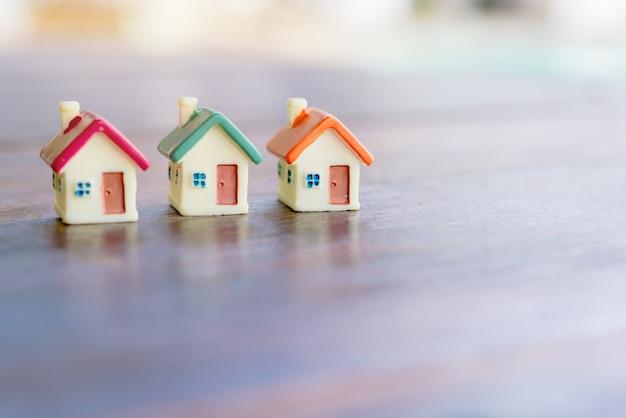 Casa miniatura sobre fondo de madera.