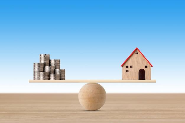 Casa modelo en balancín de equilibrio con monedas de apilamiento de dinero sobre fondo azul.