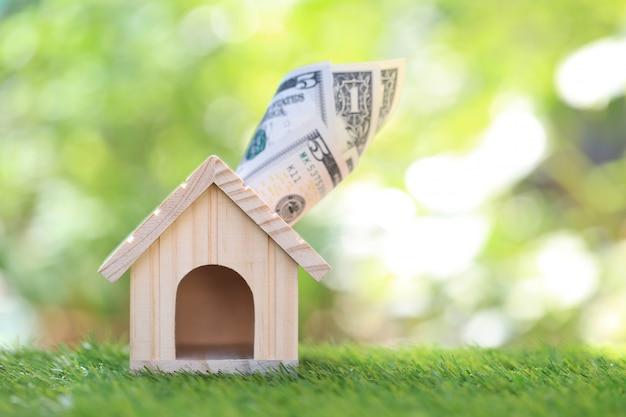 Casa modelo con billete sobre fondo verde natural, ahorro para preparar en el futuro