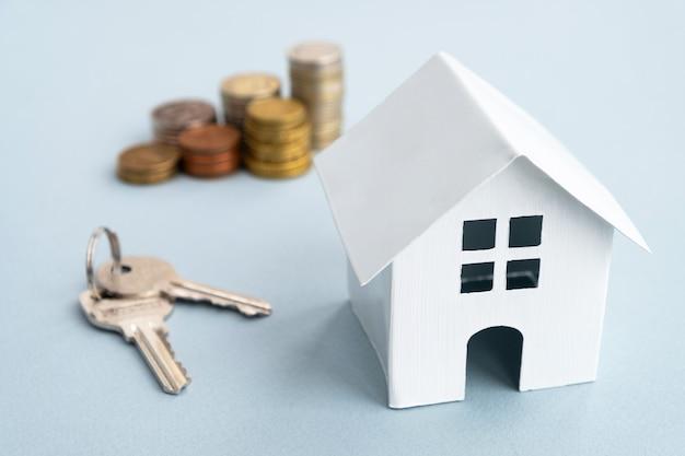 Casa modelo blanca, llaves y monedas de pila en la pared de luz
