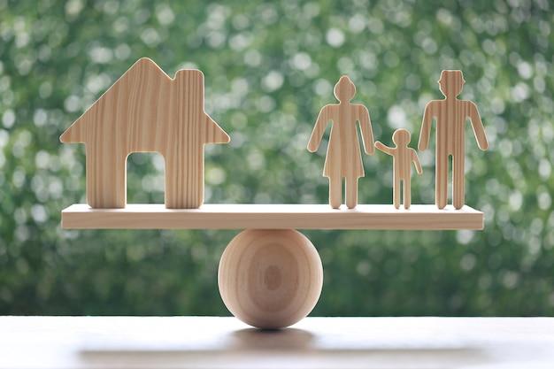 Casa modelo y familia modelo en balancín de escala de madera con fondo verde natural, hipoteca y concepto de inversión inmobiliaria