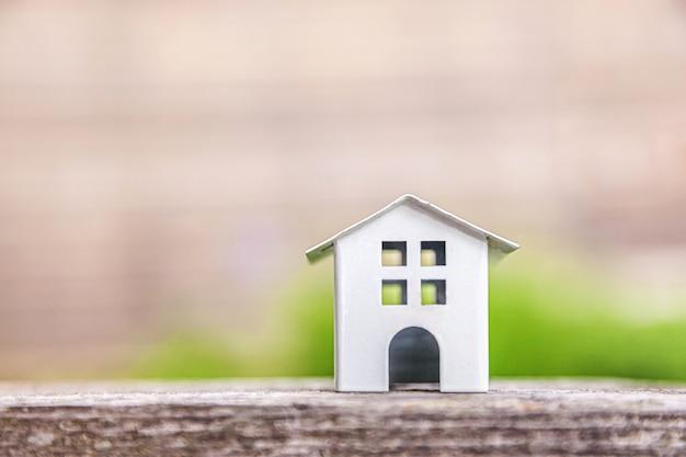Casa modelo de juguete blanco en miniatura en la mesa de madera cerca de la mesa verde