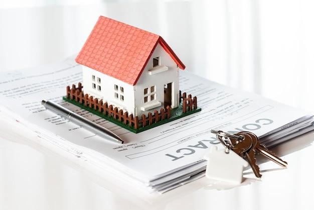 Casa modelo de juguete en una pila de documentos contractuales
