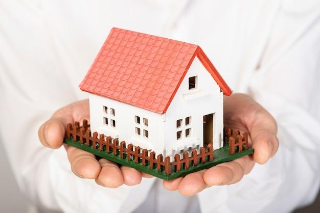 Casa modelo de juguete en primer plano de las manos