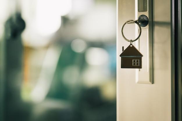 Casa modelo y llave en la puerta de la casa.