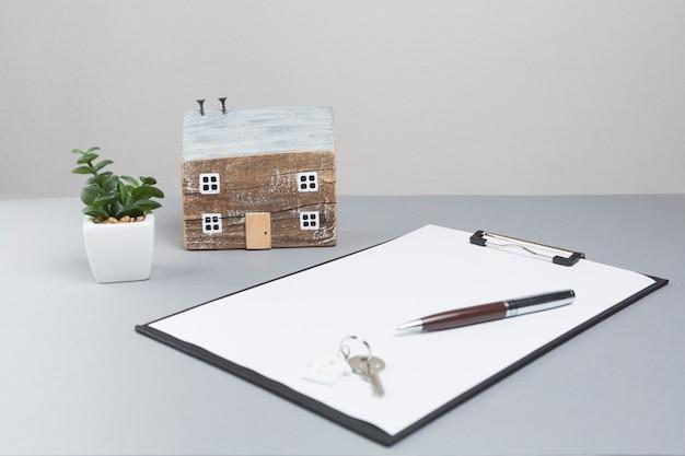 Casa modelo y llaves con portapapeles sobre superficie gris.