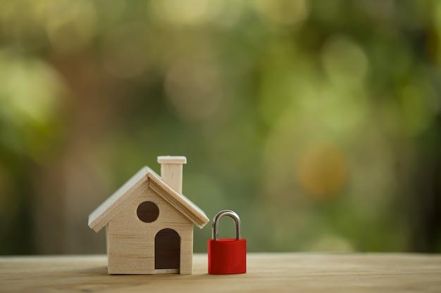 Casa modelo de madera y cerradura roja en la mesa de madera