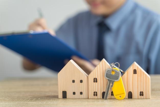 Casa modelo de madera y clave en bienes raíces, vendedor o comprador, concepto de préstamo con empleado de préstamo borroso o agente de bienes raíces que está verificando detalles sobre la venta de la casa, la hipoteca o la casa solitaria.