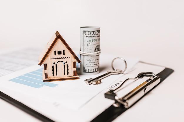 Casa modelo en miniatura y dinero en documentos.