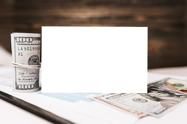 Casa modelo en miniatura y dinero con fondo en blanco sobre documentos