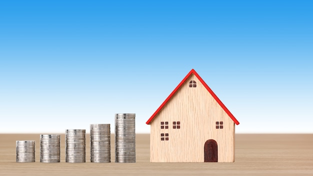 Casa modelo y monedas de apilamiento en un escritorio de madera sobre fondo azul.