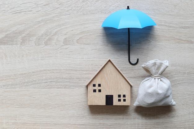 Casa modelo y paraguas sobre fondo blanco.