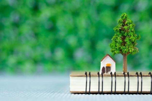 Casa modelo pequeña y arbolito con cuaderno