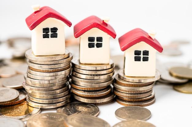 Casa en monedas de pila, concepto de préstamo hipotecario.