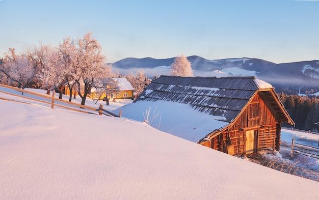Casa en las montañas en invierno. foto postal de cortesía. cárpatos, ucrania