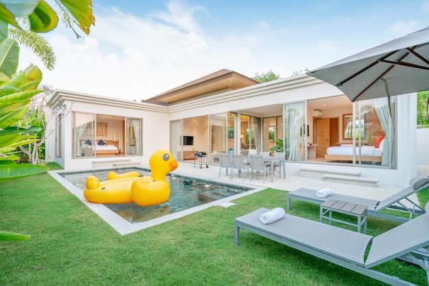Casa o casa. diseño exterior que muestra una villa con piscina tropical con zonas verdes, tumbonas y pato flotante.