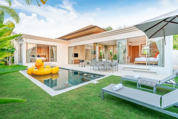 Casa o casa. diseño exterior que muestra una villa con piscina tropical con zonas verdes, tumbonas, sombrillas, toallas de piscina y pato flotante.