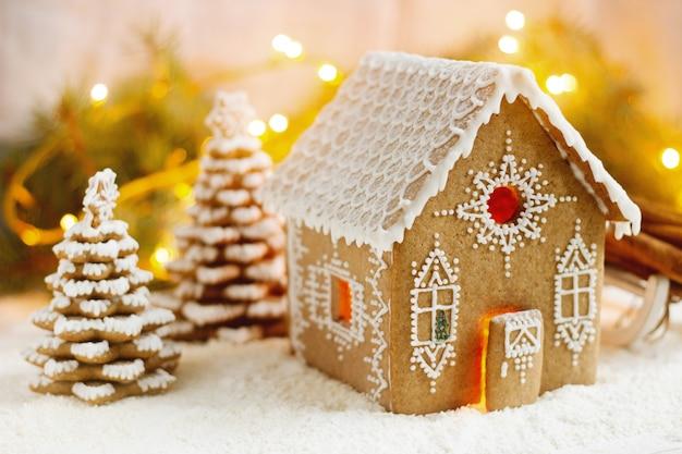 Casa de pan de jengibre y árboles de navidad en un efecto bokeh luminoso.