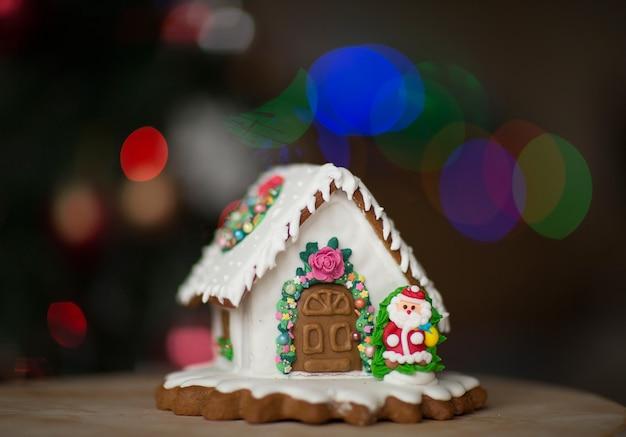 Casa de pan de jengibre blanco de navidad hecho en casa contra las luces de navidad.