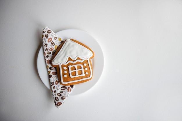 Casa de pan de jengibre de galletas de navidad aislada sobre una superficie blanca, minimalismo absoluto de invierno