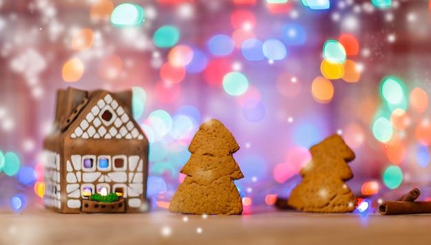 Casa de pan de jengibre y pan de jengibre comido en el fondo de navidad.