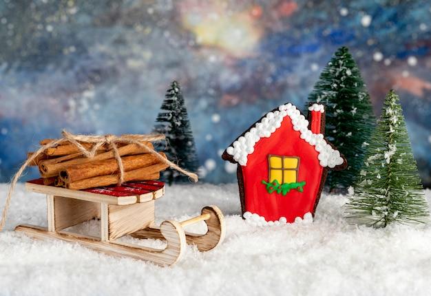 Casa de pan de jengibre, trineo de papá noel con leña de canela y tres abetos en la nieve con fondo de misterio