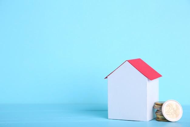 Casa de papel blanco con techo rojo, con monedas sobre fondo azul.