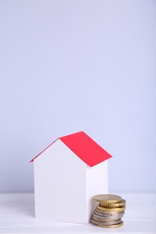 Casa de papel blanco con techo rojo, con monedas sobre fondo gris