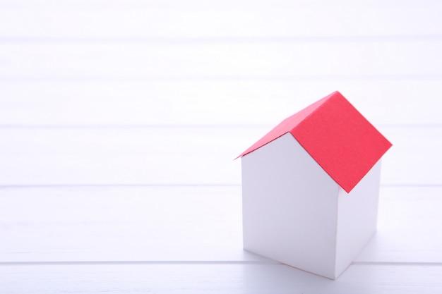 Casa de papel blanco con techo rojo sobre fondo blanco.