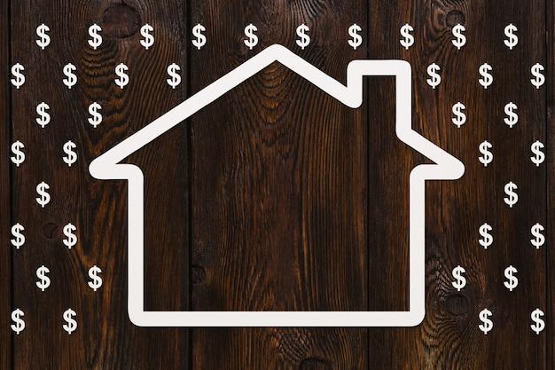 Casa de papel en lluvia de dólares sobre madera