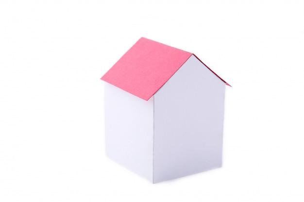 Una casa de papel con techo rojo sobre un fondo blanco.