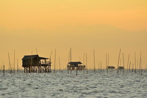 Casa de pescadores en el mar con fondo de puesta de sol de granja de mariscos en tailandia