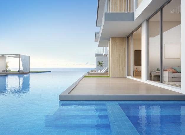 Casa de playa de lujo con piscina con vistas al mar y terraza vacía de diseño moderno.