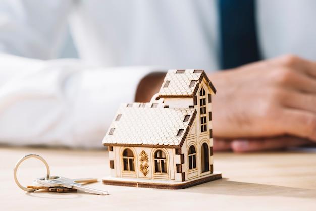 Casa de primer plano y claves cerca de agente de bienes raíces