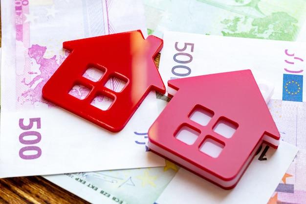 Casa roja en el paquete de pila de billetes de dólar euro. concepto inmobiliario