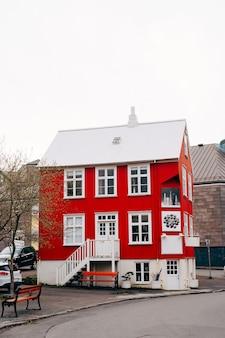 Casa roja con techo blanco en la calle en reykjavik, la capital