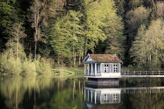 Casa sobre el agua con una orilla cubierta de hierba y árboles
