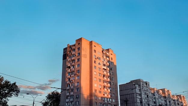 Casas de apartamentos envejecidos al atardecer con cielo azul