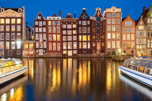 Casas de baile nocturno en el canal de amsterdam damrak, holanda, países bajos.