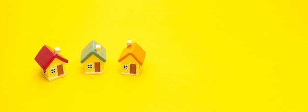 Casas de colores en miniatura sobre un fondo amarillo, espacio para texto