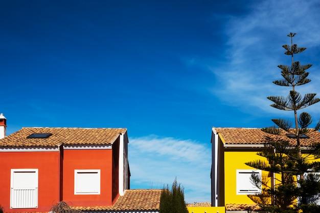 Casas con fachada de colores mediterráneos y cielo azul intenso.